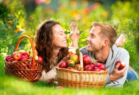 cueillette: Couple de d�tente sur l'herbe et manger des pommes � l'automne Jardin
