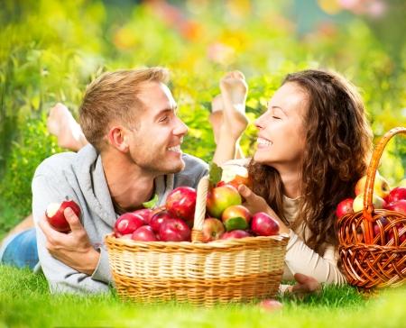 cueillette: Couple de d�tente sur l'herbe et manger des pommes dans le jardin de l'automne Banque d'images