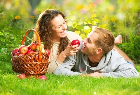 Pareja de relax en la hierba y comer manzanas en el jardín de otoño Foto de archivo