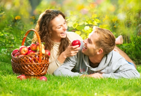 manzana roja: Pareja de relax en la hierba y comer manzanas en el jardín de otoño Foto de archivo