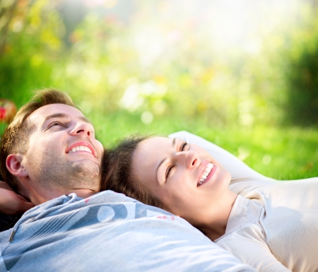 屋外の芝生の上に横たわって若いカップル 写真素材