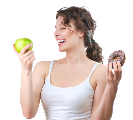 Diet  Beautiful Young Woman choosing between Fruit and Donut Stock Photo - 15353149