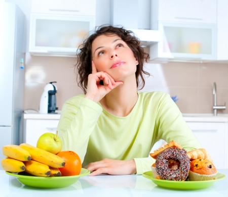 healthy choices: Diet  Beautiful Young Woman choosing between Fruits and Sweets