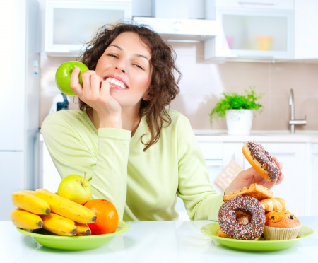 Diet  Beautiful Young Woman choosing between Fruits and Sweets  Stock Photo - 15353304