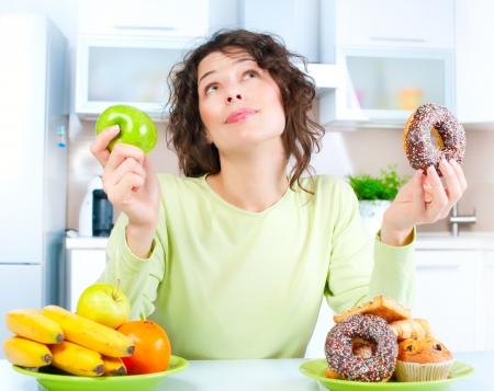 Dieta Hermosa Joven de elegir entre frutas y dulces