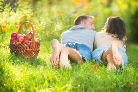 manos y pies: Pareja de relax en la hierba y comer manzanas en el jard�n de oto�o Foto de archivo