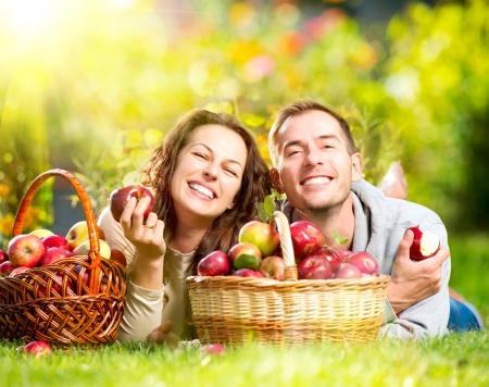 soleil souriant: Couple de d�tente sur l'herbe et manger des pommes dans le jardin de l'automne Banque d'images