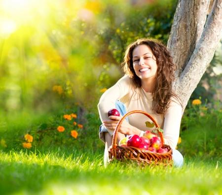 美女果樹園の有機リンゴを食べる 写真素材