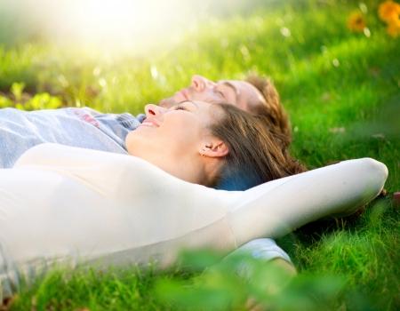 pareja abrazada: Pareja joven tumbado en la hierba al aire libre