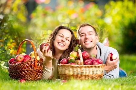 pareja comiendo: Pareja de relax en la hierba y comer manzanas en el jard�n de oto�o Foto de archivo