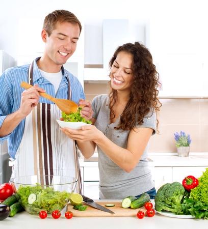 hombre cocinando: Pareja joven hombre que cocina feliz comiendo ensalada de verduras frescas Foto de archivo
