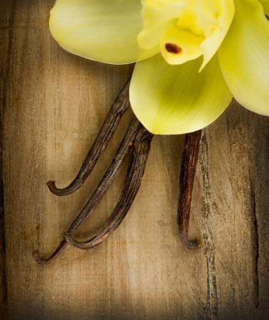 flores exoticas: Las vainas de vainilla y flores sobre fondo de madera Foto de archivo
