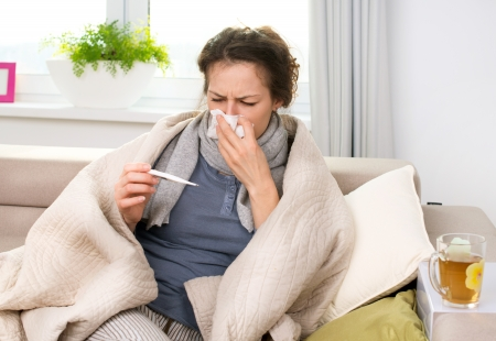 gripe: Mujer enferma con gripe estornuda termómetro en el tejido Foto de archivo