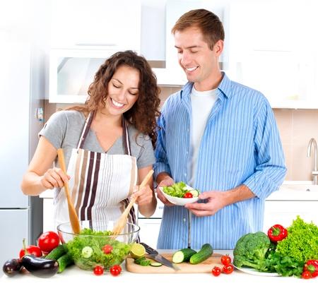 mujeres cocinando: Cocinar Joven Pareja Juntos Ensalada Vegetal Foto de archivo