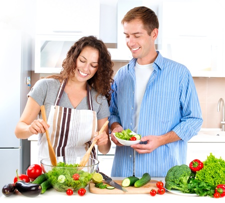 woman cooking: Young Couple Cooking Vegetable Salad Together