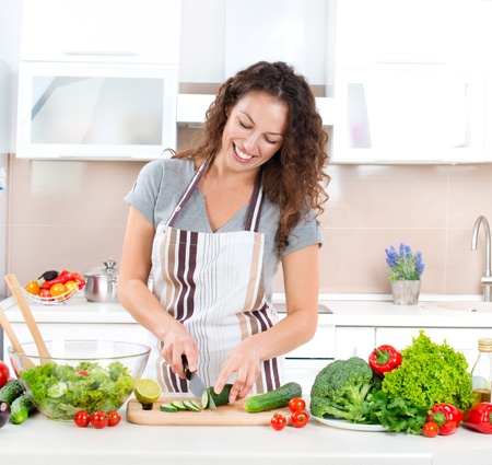 Young Woman Cooking Healthy Food - Vegetable Salad Stock Photo
