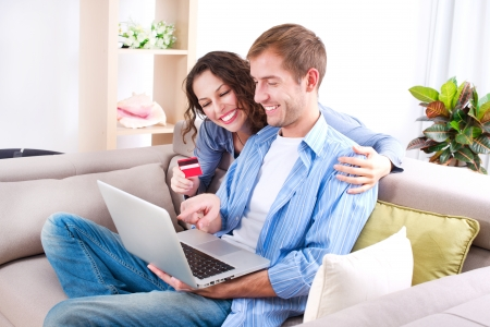 shopping man: Young couple with Laptop and Credit Card buying online