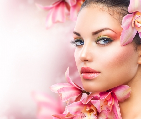 La bella ragazza con i fiori dell'orchidea fiorisce il fronte della donna Archivio Fotografico - 16472446