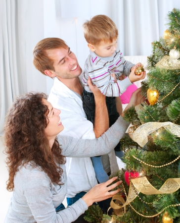 home decorating: Young Family decorating a Christmas Tree  Stock Photo