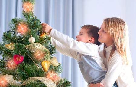 decorating christmas tree: Kids Decorating Christmas Tree  Happy Children Stock Photo