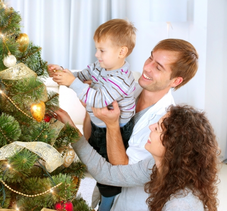 decorating christmas tree: Young Family decorating a Christmas Tree  Stock Photo