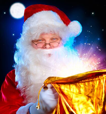 Christmas Santa  Santa Claus opening Magic Bag with Gifts  Christmas Santa  Santa Claus opening Magic Bag with Gifts  photo