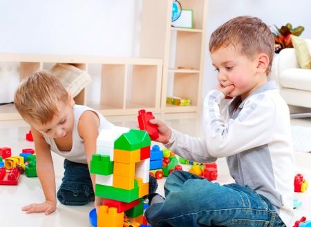enfants qui jouent: Gar�ons Enfants jouant avec jeu de construction sur le sol Banque d'images