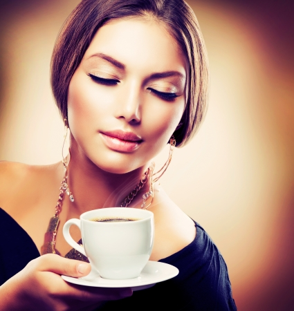 Beautiful Girl Drinking Tea or Coffee  Sepia Toned photo