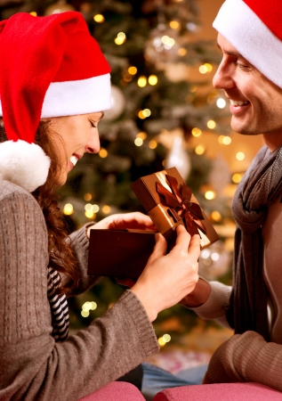 Christmas Scene  Happy Couple with Christmas Gift at Home  photo