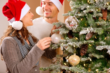 Happy Couple Decorating Christmas Tree in their Home photo