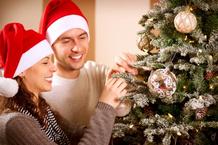 decorating christmas tree: Happy Couple Decorating Christmas Tree in their Home