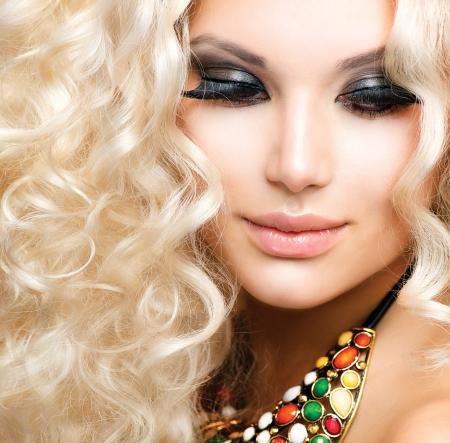 secador de pelo: La muchacha hermosa con el pelo rubio y rizado