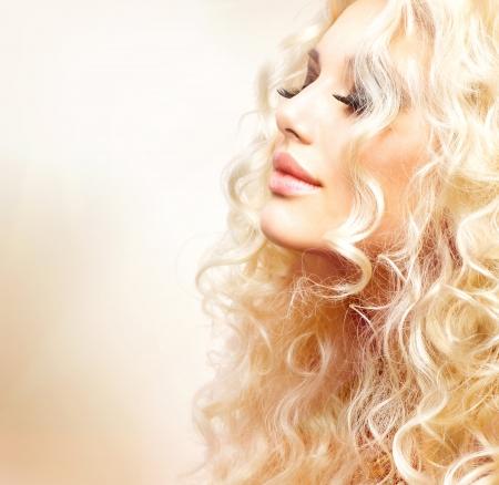hair dryer: La muchacha hermosa con el pelo rubio y rizado