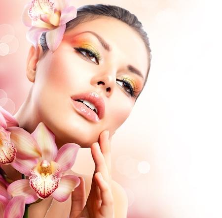 Fille magnifique spa avec des fleurs d'orchidées toucher son visage