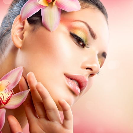face close up: Beautiful Spa Girl With Orchid Flowers Touching her Face