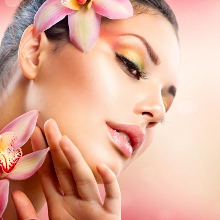 gezicht: Mooie Spa Meisje Met Orchidee Bloemen te raken haar gezicht