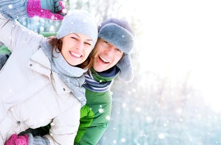 ropa de invierno: Pareja feliz que se divierte al aire libre de nieve Vacaciones de invierno