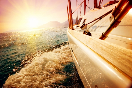 sailing: Yacht Sailing against sunset  Sailboat  Yachting  Sailing Stock Photo