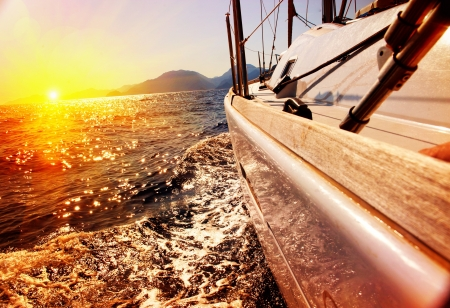 sail boat: Yacht Sailing against sunset  Sailboat  Yachting  Sailing Stock Photo