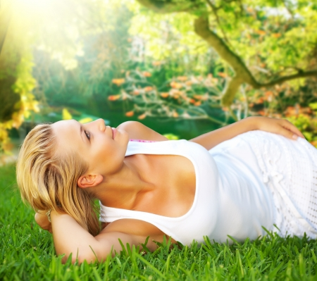 spring time: Beautiful healthy Young Woman relaxing on the green grass