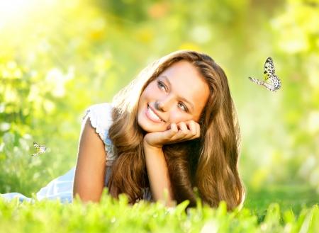 屋外の緑の草の上に横たわる春美美しい女の子