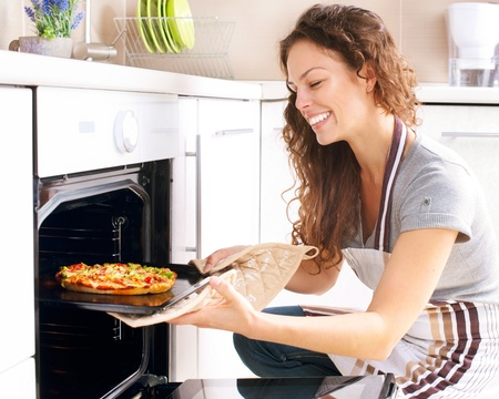 pizza oven: Happy Young Woman Cooking Pizza at Home Stock Photo