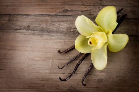Vanilla Pods and Flower over Wooden Background  photo
