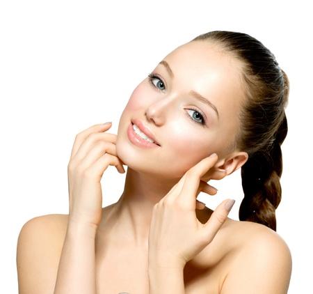 Mujer hermosa joven con la piel limpia y fresca que toca su cara