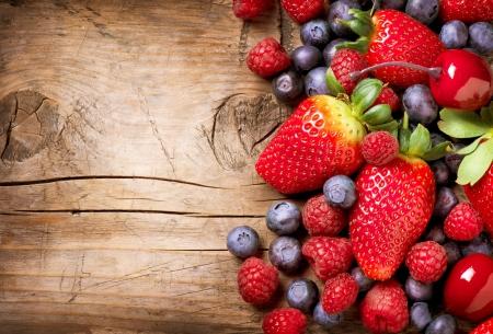 juice fruit: Frutti di bosco su fondo in legno Berry Organic su legno Archivio Fotografico