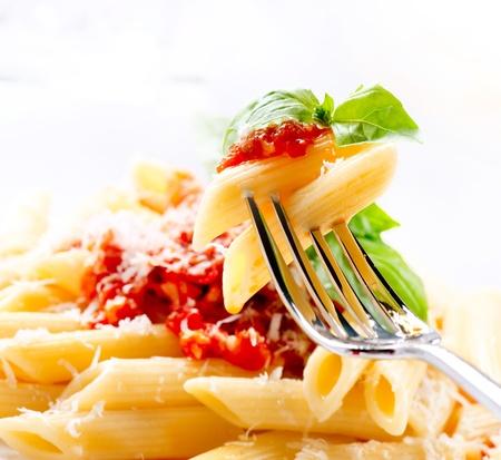 lunchen: Pasta Penne met Bolognese saus, basilicum en Parmezaanse Stockfoto
