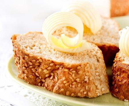 mantequilla: Mantequilla sobre una rebanada de pan de mantequilla Rolls Desayuno Saludable Foto de archivo