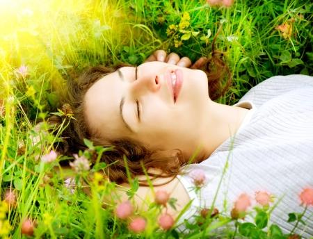 美しい若い女性は屋外を楽しむ自然草原