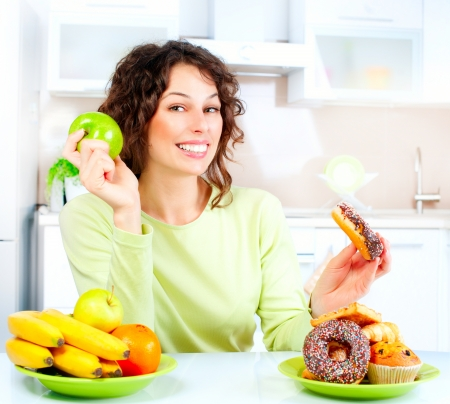 healthy choices: Dieting concept  Young Woman choosing between Fruits and Sweets  Stock Photo