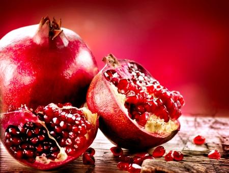 Melograni su sfondo rosso organici frutta Bio Archivio Fotografico